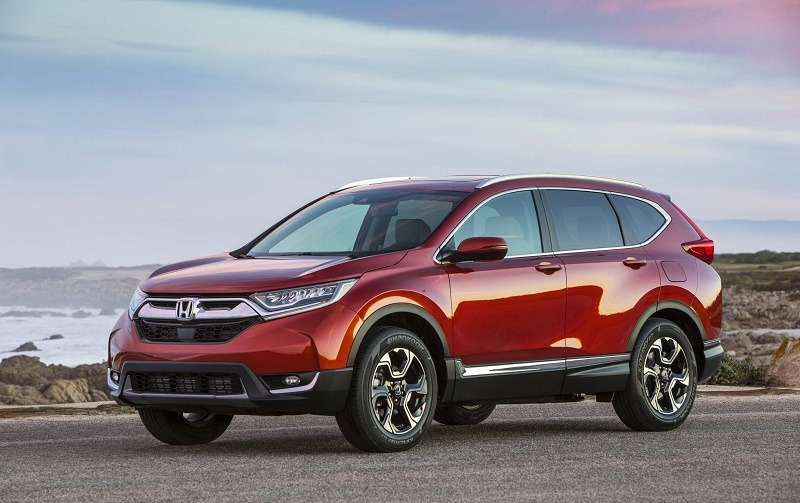View of 2017 Honda CR-V in burnt orange at sunset with ocean in background