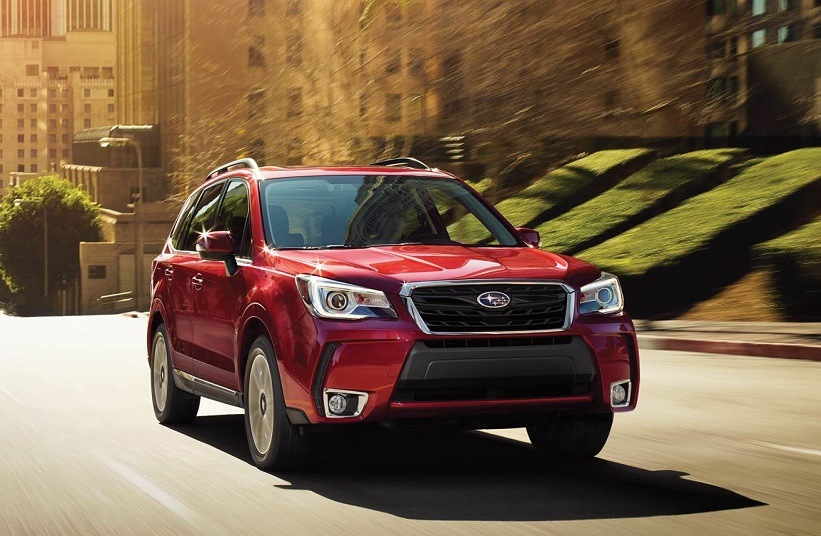 View of red Subaru Forester, model year 017, driving down a city street at sunset