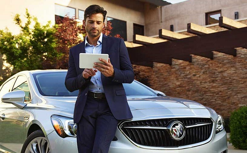 View of man holding tablet while leaning on 2017 Buick LaCrosse
