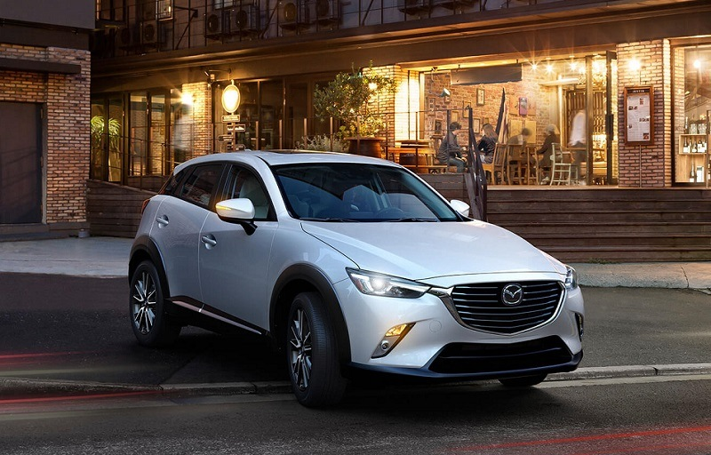View of ceramic metallic 2017 Mazda CX-3 parked outside an urban cafe