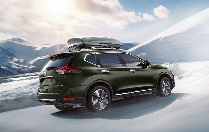 View of green 2017 Rogue driving on snow