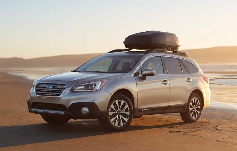 View of Subaru Outback on the beach at sunrise
