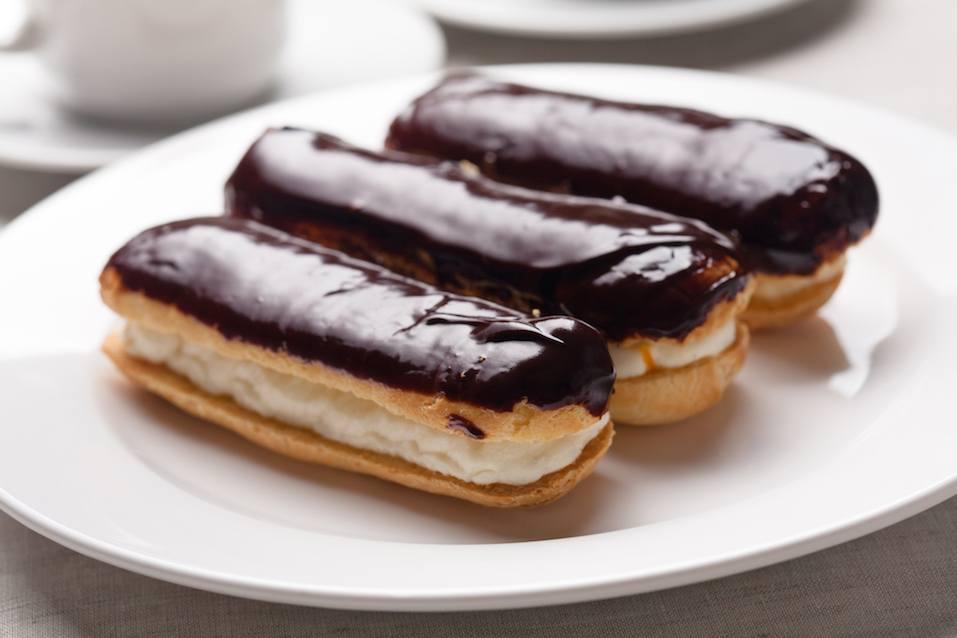 three chocolate cream eclairs on a white plate