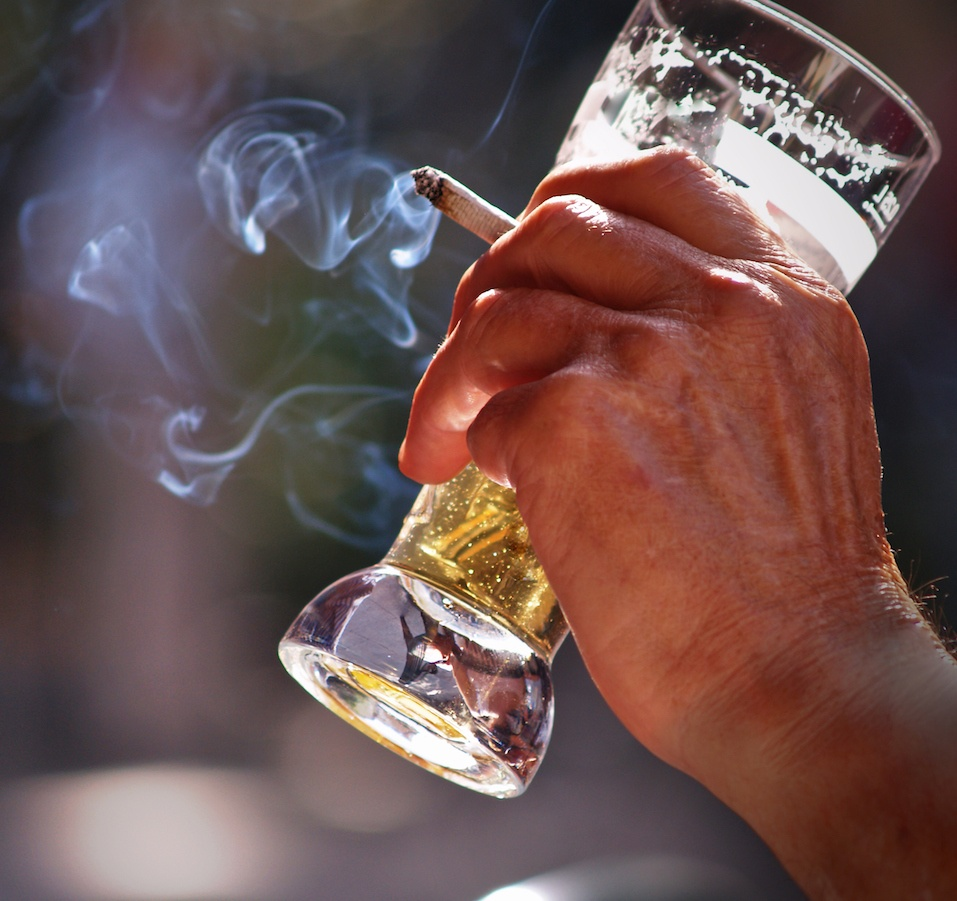 Man sitting at the table in outdoor pub Drinking beer and smoking