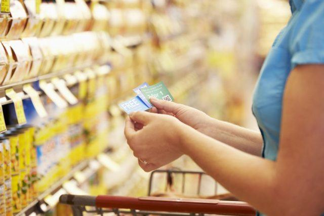 woman looking at coupons in grocery store aisle