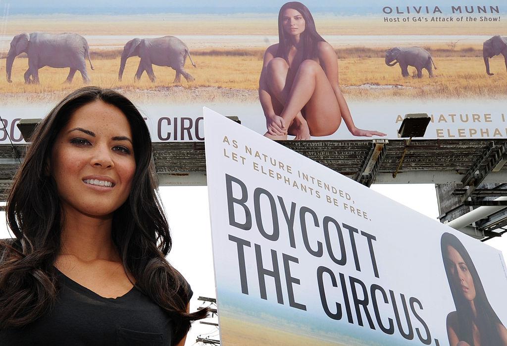 "Actress Olivia Munn beside her billboard that says ""boycott the circus"""