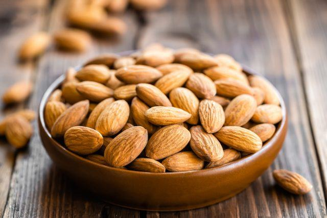 Almonds in a bowl on a wooden table.