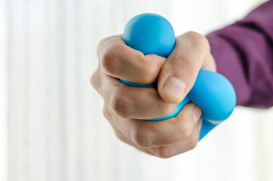 Anti-stress balls in hand, according to the window with bright sunlight