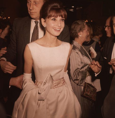 Belgian-born actress Audrey Hepburn wearing a white satin evening gown and long gloves.