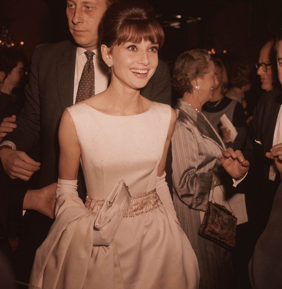 Belgian-born actress Audrey Hepburn (1929 - 1993) wearing a white satin evening gown and long gloves
