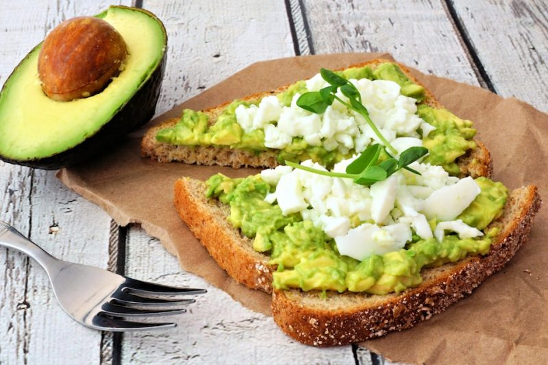 Avocado toast with egg whites and pea shoots on paper against a white wood background