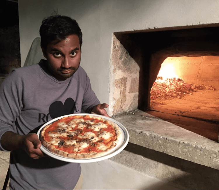 Aziz Ansari with a pizza