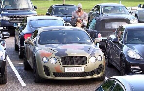 Picture of Italian soccer star Mario Balotelli approaching his camouflage Bentley in a parking lot