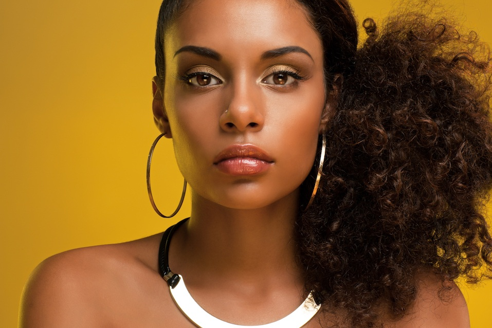 Beautiful African-American woman wearing golden jewelry and posing in front of a yellow background