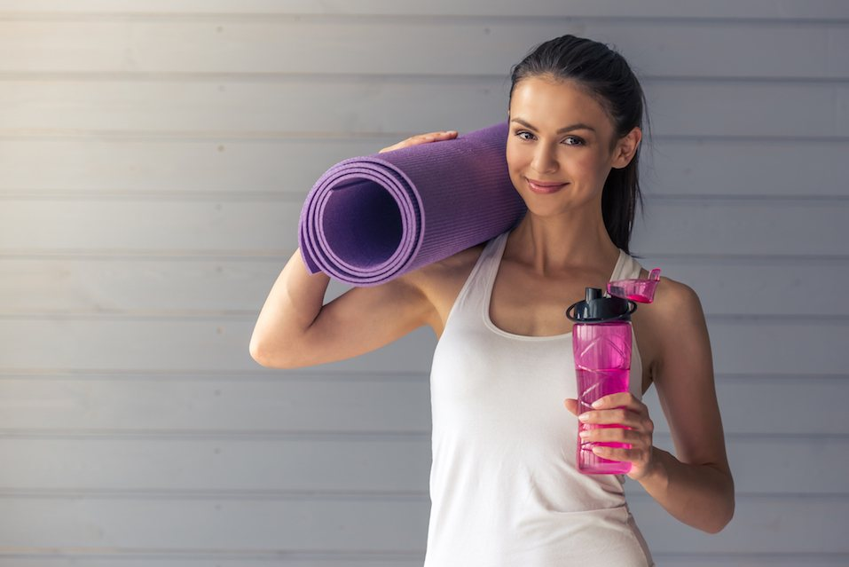 Beautiful young woman in sports wear is holding a yoga mat and a bottle of wate