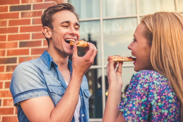 young couple is eating pizza