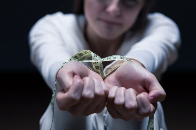 Woman's hands tied by a measuring tape.