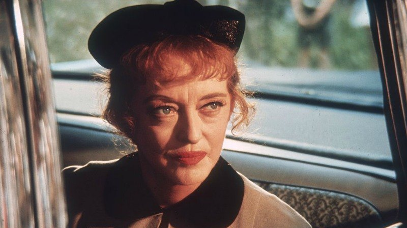 Bette Davis is sitting in a car and is wearing a black hat.
