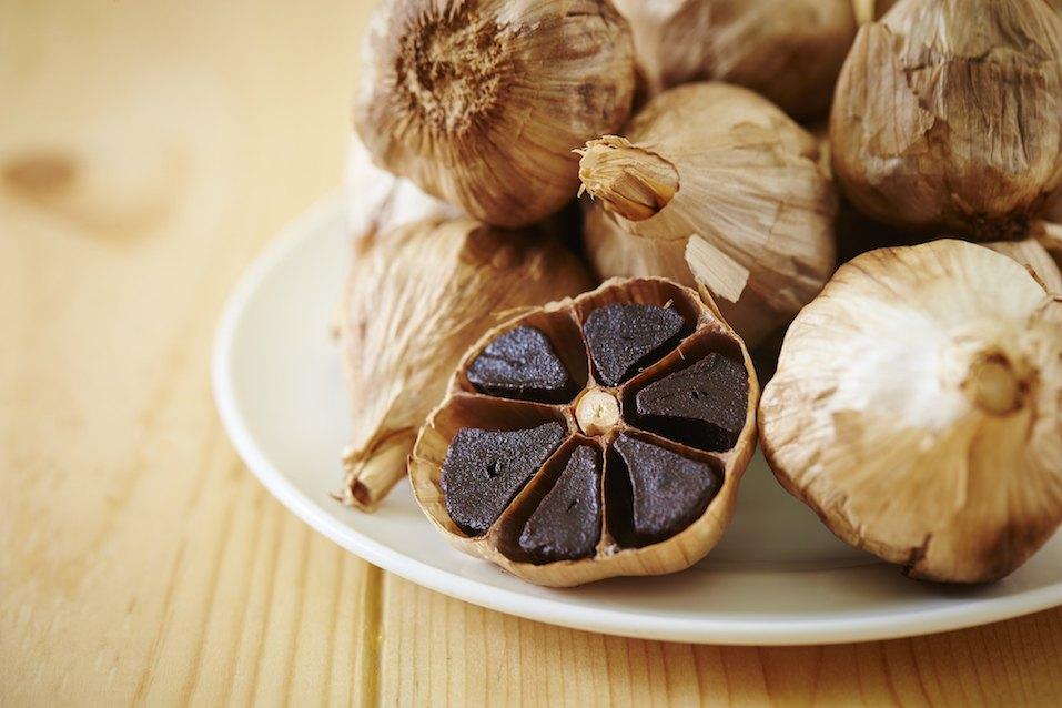 Black garlic on dish, wooden background