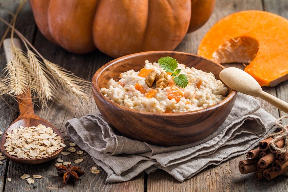 Breakfast oatmeal porridge with pumpkin in a wooden bowl on wooden background
