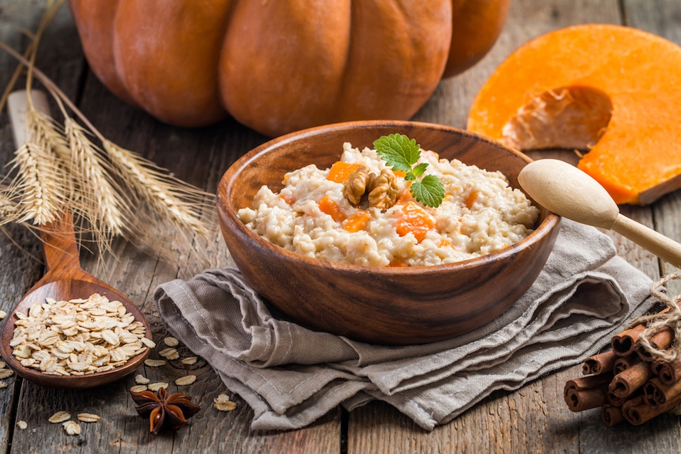 Breakfast oatmeal porridge with pumpkin in a wooden bowl on wooden background
