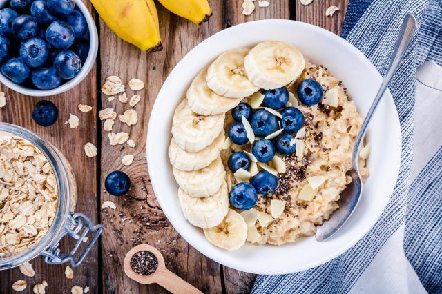 Oatmeal with bananas, blueberries, chia seeds on a wooden table.