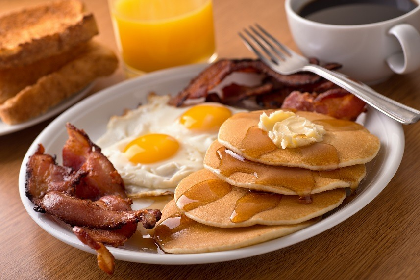 Bacon, eggs, pancakes, toast, coffee, and orange juice