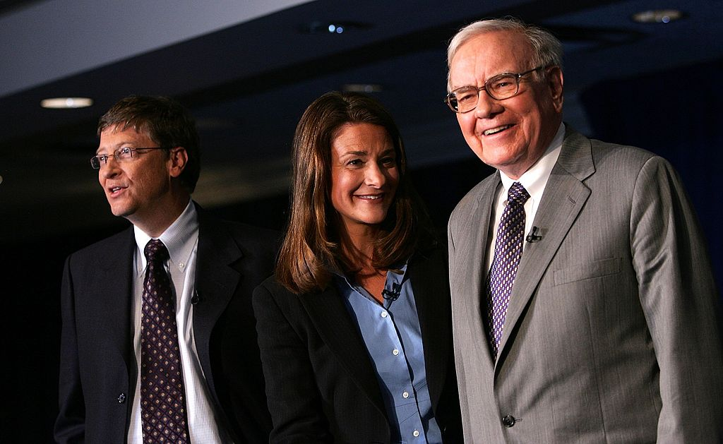 Warren Buffett stands with Bill and Melinda Gates