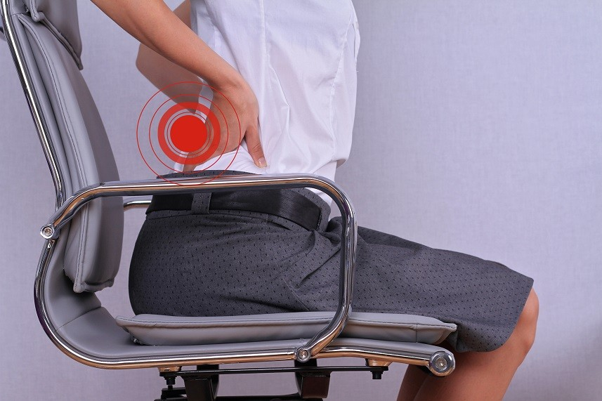 woman with back pain sitting in an office chair