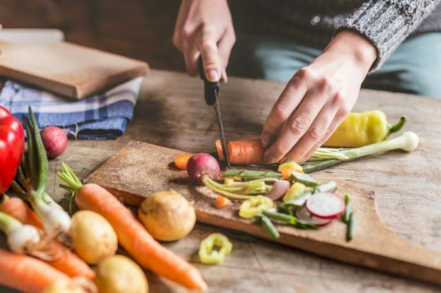 Woman Chopping food on a wooden board with a knife.