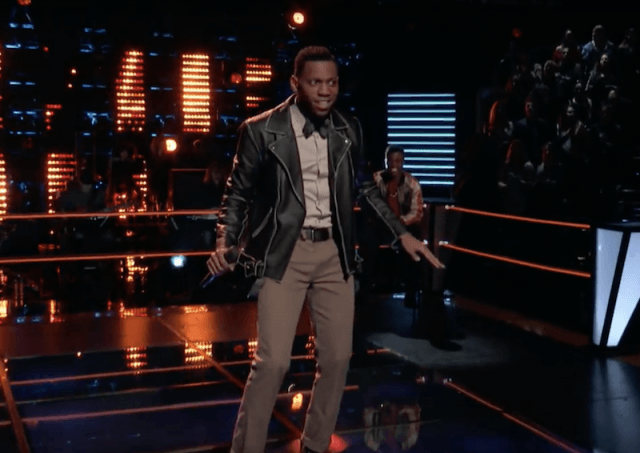 Chris Blue dancing and singing on stage in a leather jacket.