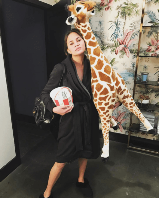 Chrissy Teigen with a bucket of fast food and a stuffed giraffe