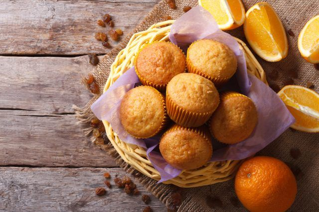 Muffins surrounded by citrus fruits on a wooden table