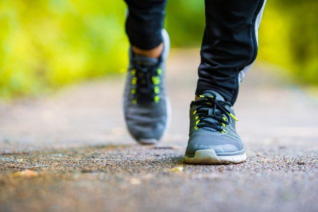 person in running shoes walking on paved path