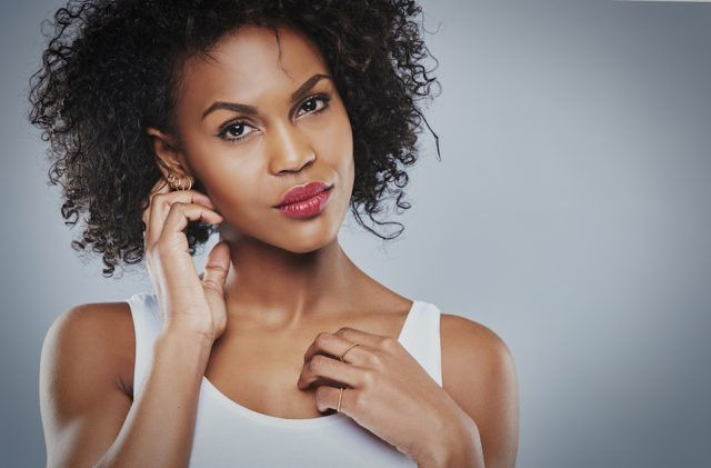 beautiful black woman with big curly hair in white top, isolated on grey background