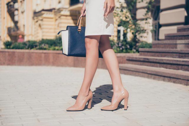 Close up of slim legs of woman wearing high heel shoes
