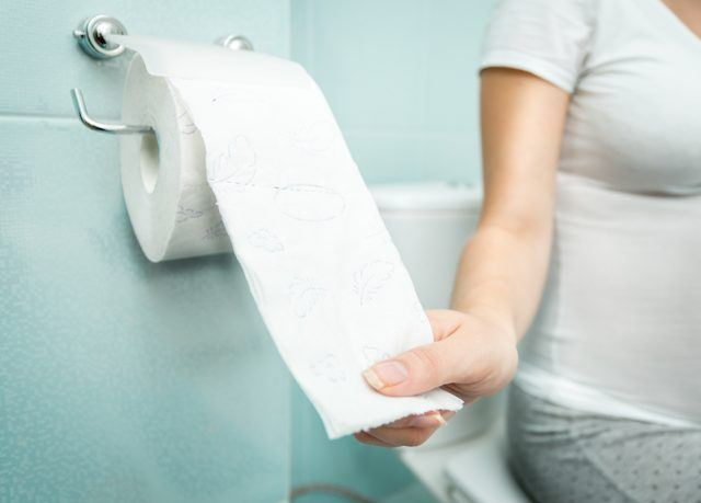 Closeup photo of woman sitting on toilet and using toilet paper.
