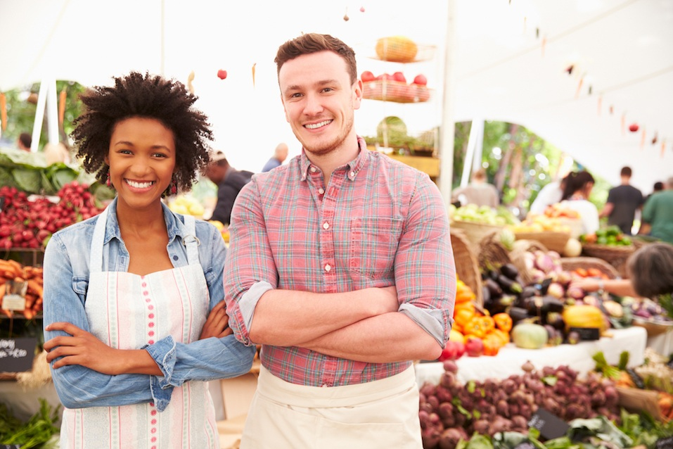 Couple Running Stall At Farmers Fresh Food Market, Smiling To Camera