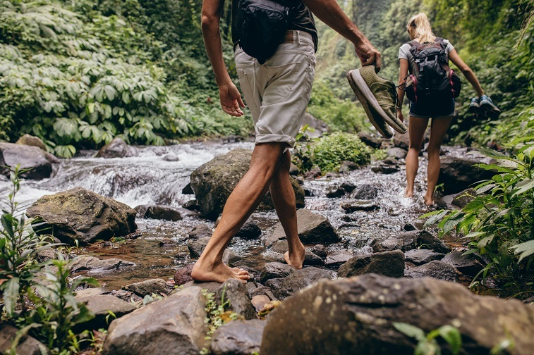 man and woman crossing the stream