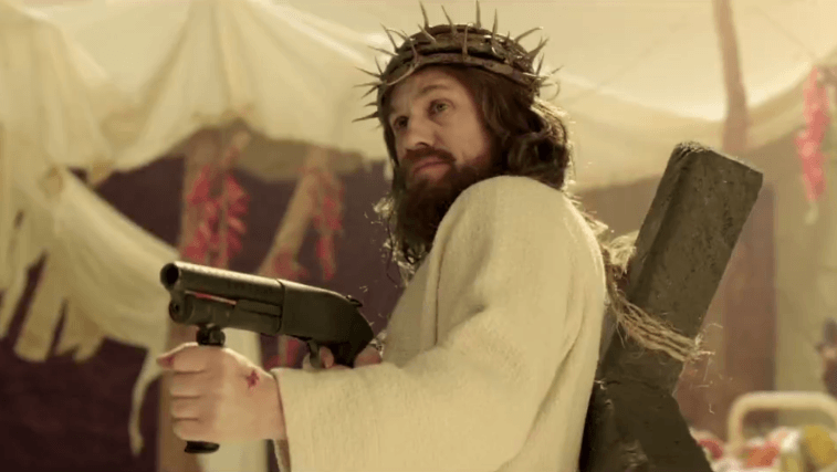 Christoph Waltz holds a machine gun dressed as Jesus.