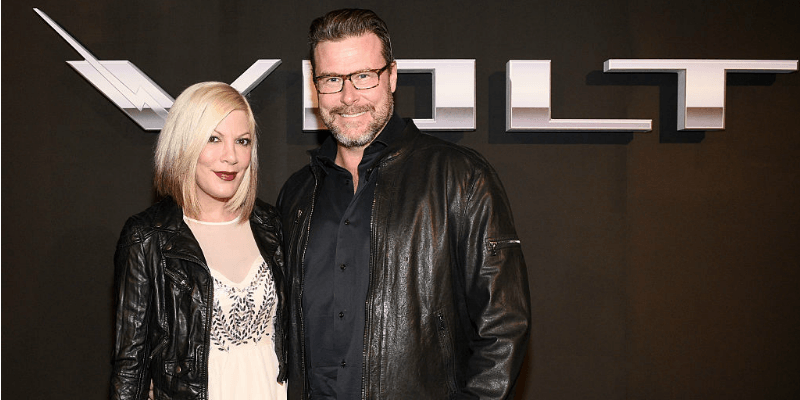 Tori Spelling and Dean McDermott pose together in front of a Volt sign.