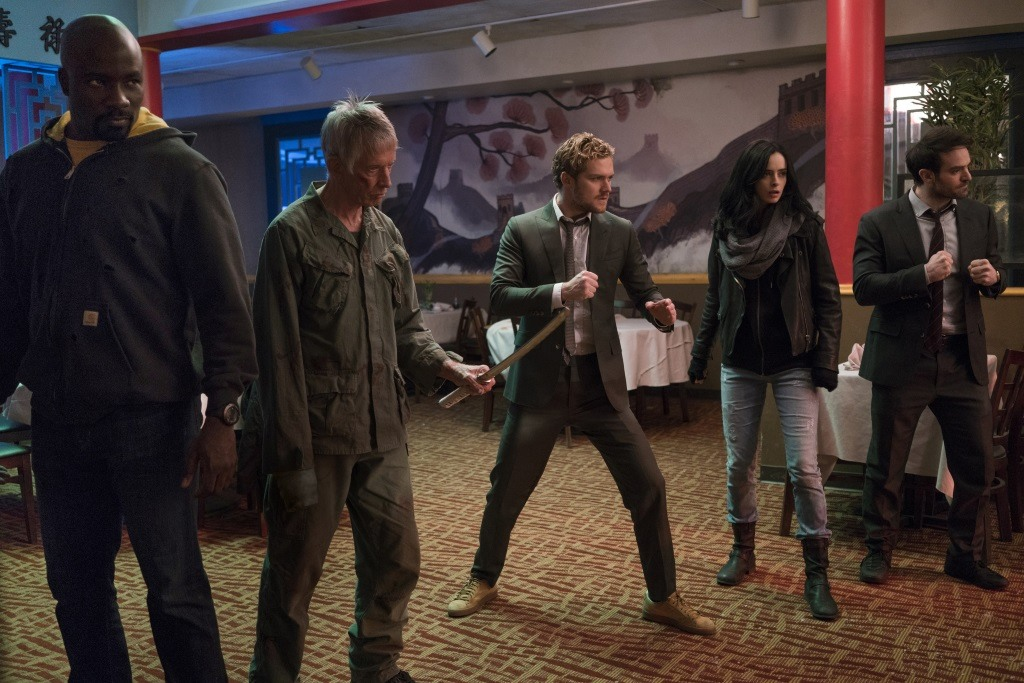 Mike Colter, Scott Glenn, Finn Jones, Krysten Ritter, and Charlie Cox standing in a row in a restaurant
