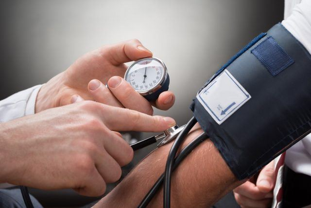 A doctor checks a patient's blood pressure.