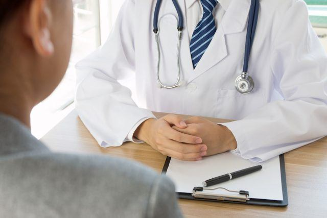 Doctor and patient talking across a table.