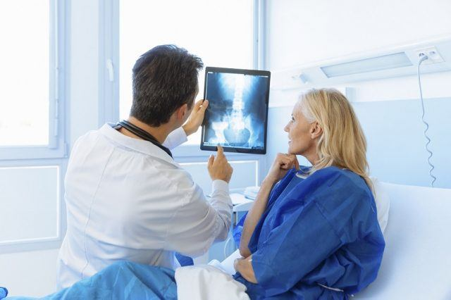 Doctor showing xray to a patient.