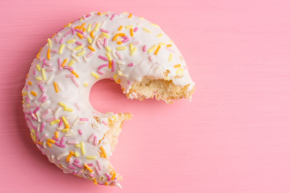 Donut with sprinkles on the pink background