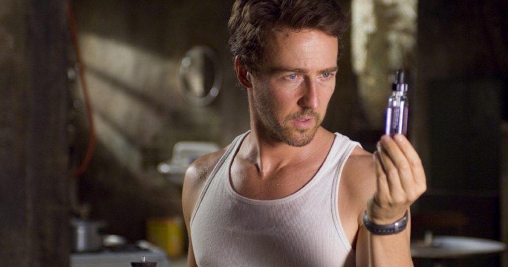 Ed Norton as Bruce Banner, wearing a white tank top and looking at a purple vial in his hand