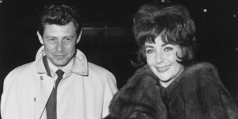 Eddie Fisher is wearing a trench coat next to Elizabeth Taylor who has a fur coat.