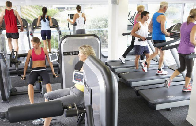 Busy Gym With People Exercising On Machines