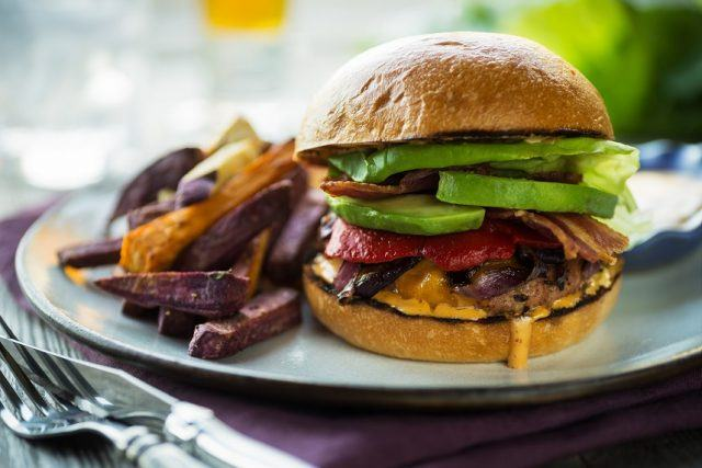 large cheeseburger stacked with avocado and veggies